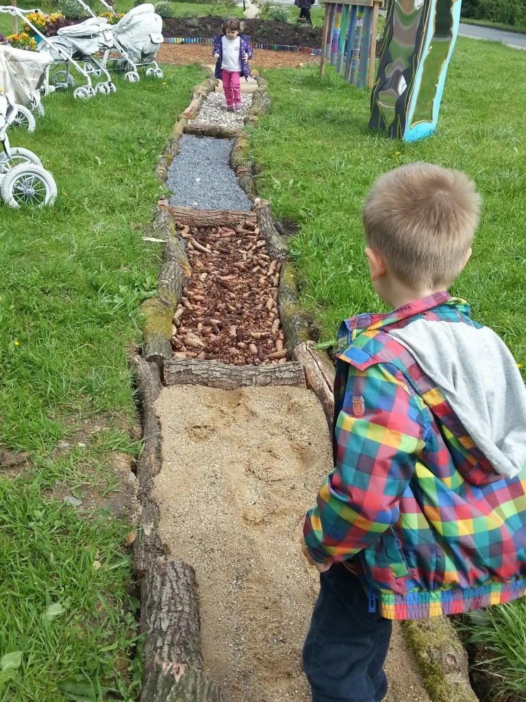 Der Weg mit den verschiedenen Untergründen: Steine, Sand, Holz, Mulch, Tannenzapfen etc.